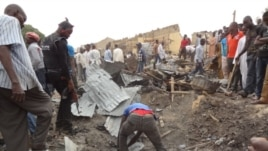 A day after a double bombing in northern Nigeria killed dozens of people, men search the rubble for bodies in Maidguri, March 2, 2014. (Abdulkareem Haruna/VOA)
