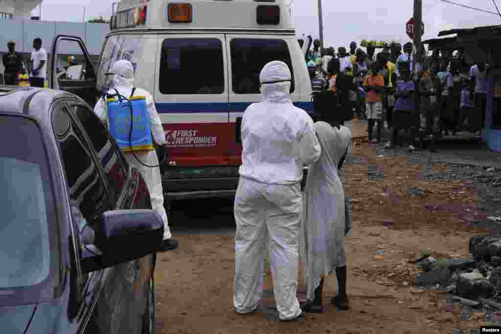 Health workers bring a woman suspected of having contracted Ebola virus to an ambulance in Monrovia, Liberia, Sept. 15, 2014.