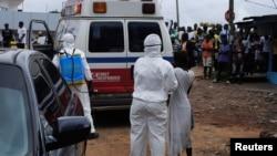 Petugas kesehatan membawa seorang perempuan yang diduga tertular Ebola ke sebuah ambulans di Monrovia, Liberia (15/9). Militer AS akan membangun pusat komando misi pemberantasan Ebola di Monrovia.