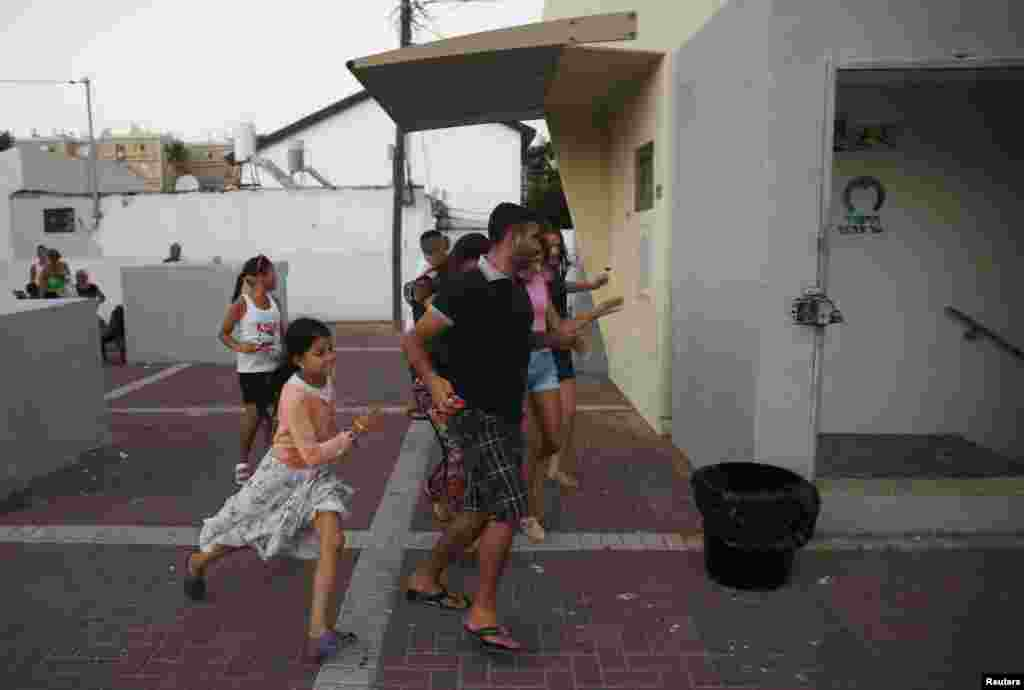 Israelis run towards a bomb shelter as a siren sounds warning of incoming rockets in the southern city of Ashkelon, July 9, 2014.