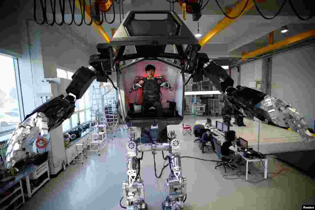 "An employee controls the arms of a manned biped walking robot ""METHOD-2"" during a demonstration in Gunpo, South Korea."