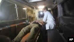 2016年8月24日阿富汗美国大学遭袭后救护人员抢救受伤人员。