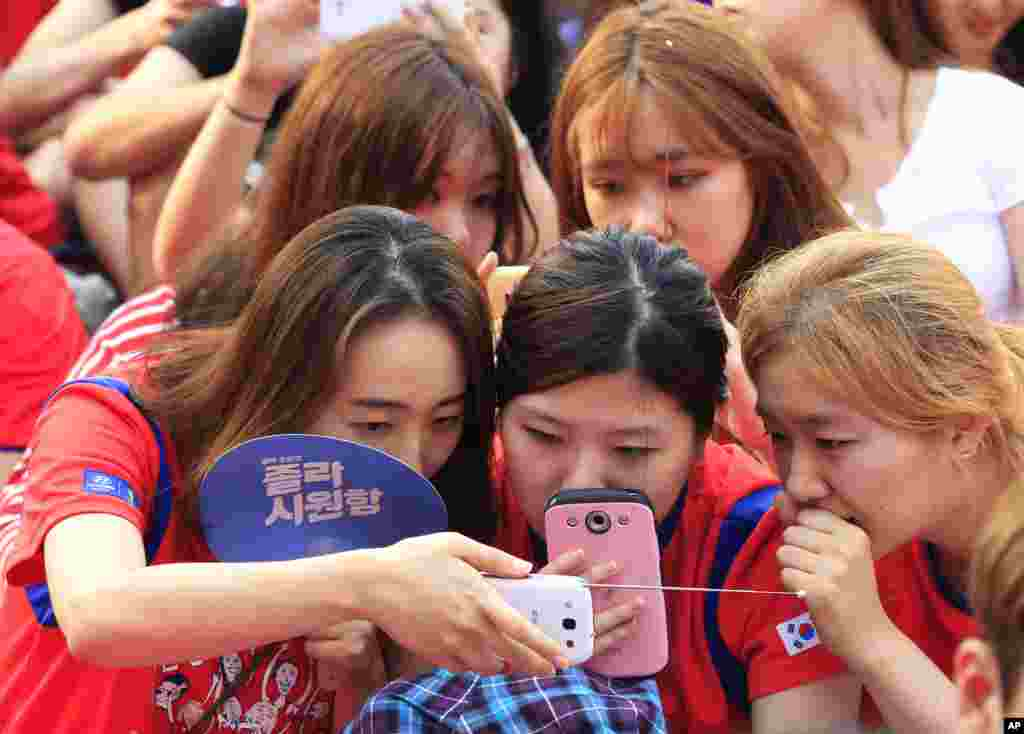 South Korean soccer fans watch a live broadcast of World Cup soccer match between Russia and South Korea on smartphones.  The large screen was turned off due to a network error at a public viewing venue in Seoul, South Korea.