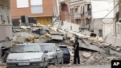A police officer looks at the damage in Lorca, Spain a day after an earthquake hit the region, May 12, 2011.