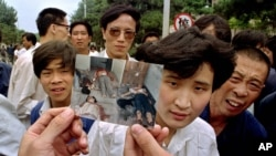 FILE- In this file photo taken June 5, 1989, people on Chang'an Boulevard hold up a photo that they described as dead victims of the violence against pro-democracy protesters on Tiananmen Square, Beijing. Hundreds had been killed in the early morning hours.
