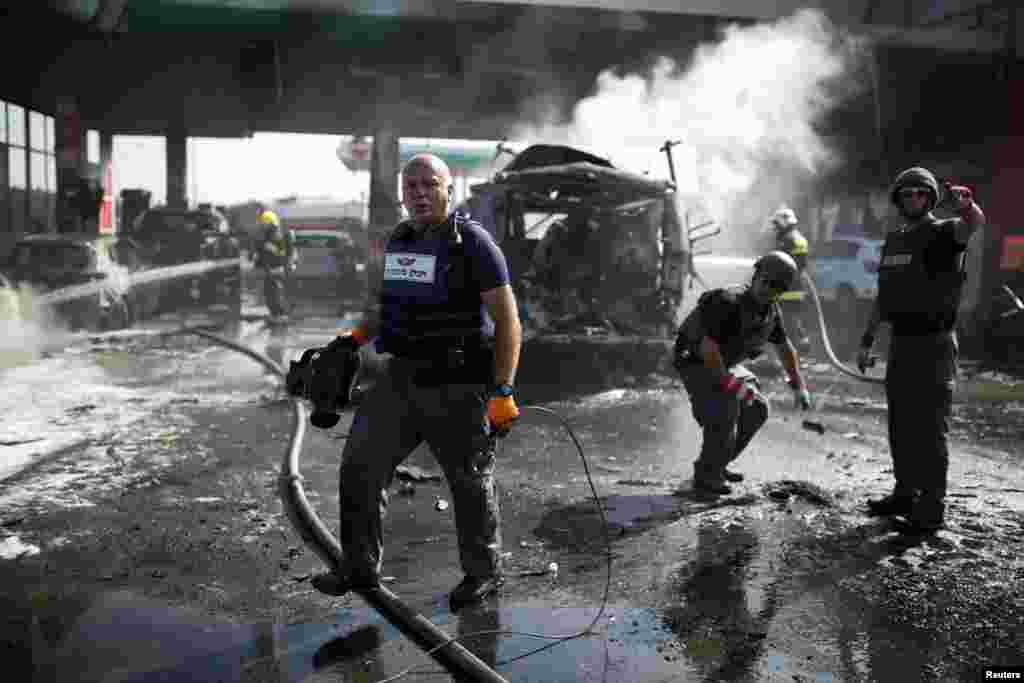 Israeli police explosive experts survey the scene at a gas station after it was hit by a rocket in the southern city of Ashdod, Israel, July 11, 2014.