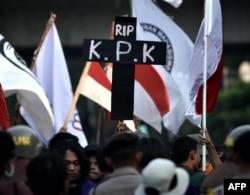 Seorang mahasiswa menunjukkan poster simbol kematian Komisi Pemberantasan Korupsi dalam demonstrasi di gedung DPR/MPR di Jakarta, 1 Oktober 2019. (Foto: AFP)