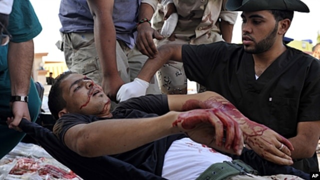 Libyan revolutionary fighters transport an injured man to a field hospital outside Sirte, Libya, September 30, 2011.