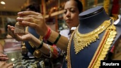 FILE - A saleswoman shows a gold earring to customers at a showroom in Mumbai, India.