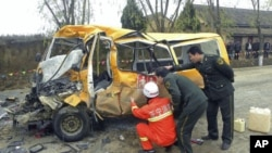 Rescuers inspect a school bus after it collided with a truck [not seen] in Yulinzi township of Zhengning county, Gansu province, November 16, 2011.