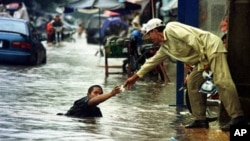 A Cambodian amputee beggar is given money by a passerby while wading in the street flood in Phnom Penh.