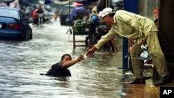 A Cambodian amputee beggar is given money by a passerby while wading in the street flood in Phnom Penh, file photo.