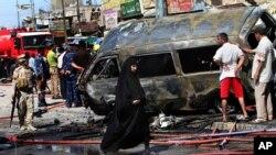 Warga dan petugas keamanan memeriksa lokasi kejadian ledakan bom di Basra, sebelah tenggara Baghdad (29/7).