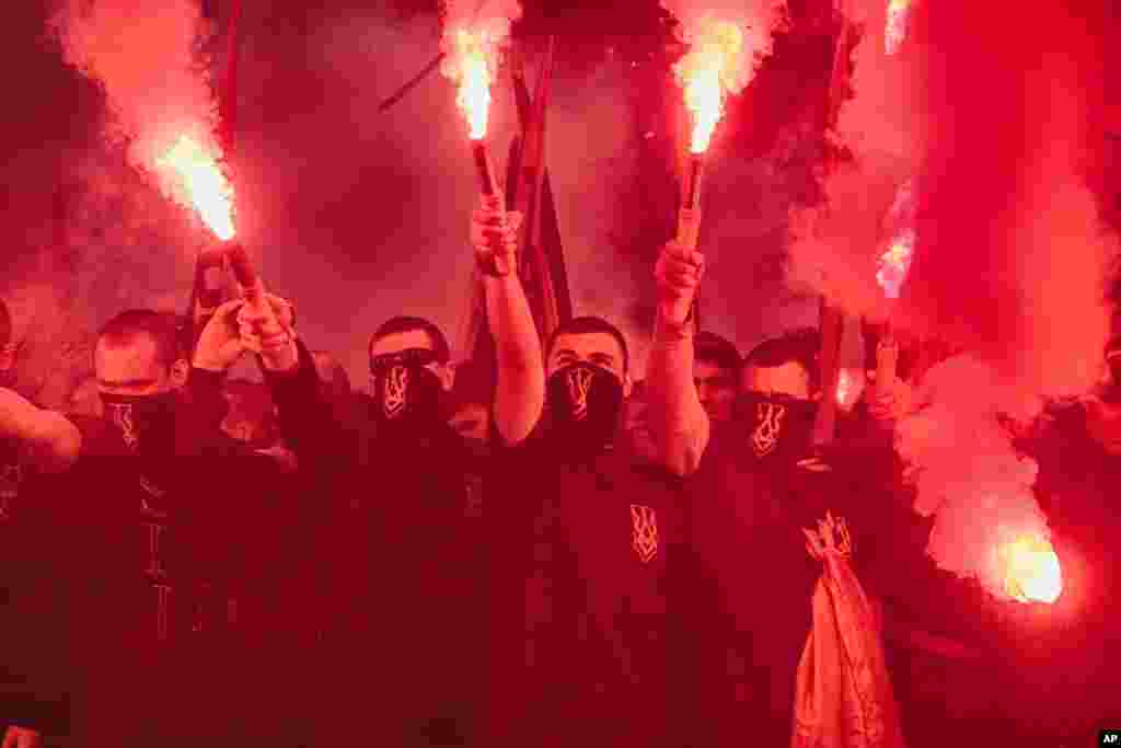 Volunteers of the Azov Civil Corps hold flares during rally at the Ukrainian Parliament against holding local elections in the occupied eastern territories of Ukraine.