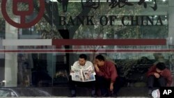 In this undated file photo, men in Guangzhou, southeastern Guangdong province, share a newspaper outside a branch of the state-run Bank of China, which recently halted business with North Korea's Foreign Trade Bank, in the latest sign of Beijing-Pyongyang tensions.
