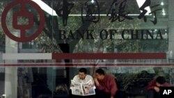 Dua pria membaca koran di depan kantor cabang Bank of China, di Guangzhou, selatan provinsi Guangdong (Foto: dok).