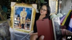 A shopkeeper show portraits of Thailand's Crown Prince Vajiralongkorn to a customer outside of her shop in Bangkok, Thailand, Thursday, Dec. 1, 2016.