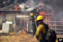 Firefighters battle flames as a house burns in Lower Lake, Calif., on Aug. 14, 2016. The fire reached Main Street in Lower Lake, a town of about 1,200 about 90 miles north of San Francisco