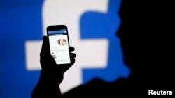 FILE - man is silhouetted against a video screen with an Facebook logo as he poses with an Samsung S4 smartphone in this photo illustration taken in the central Bosnian town of Zenica, August 14, 2013.
