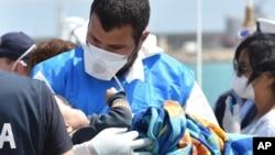 Seorang petugas paramedik memegang bayi yang dibungkus selimut di tengah kedatangan migran di pelabuhan Pozzallo dekat Ragusa, Sisilia di Italia (19/5). (AP/Carmelo Imbesi)
