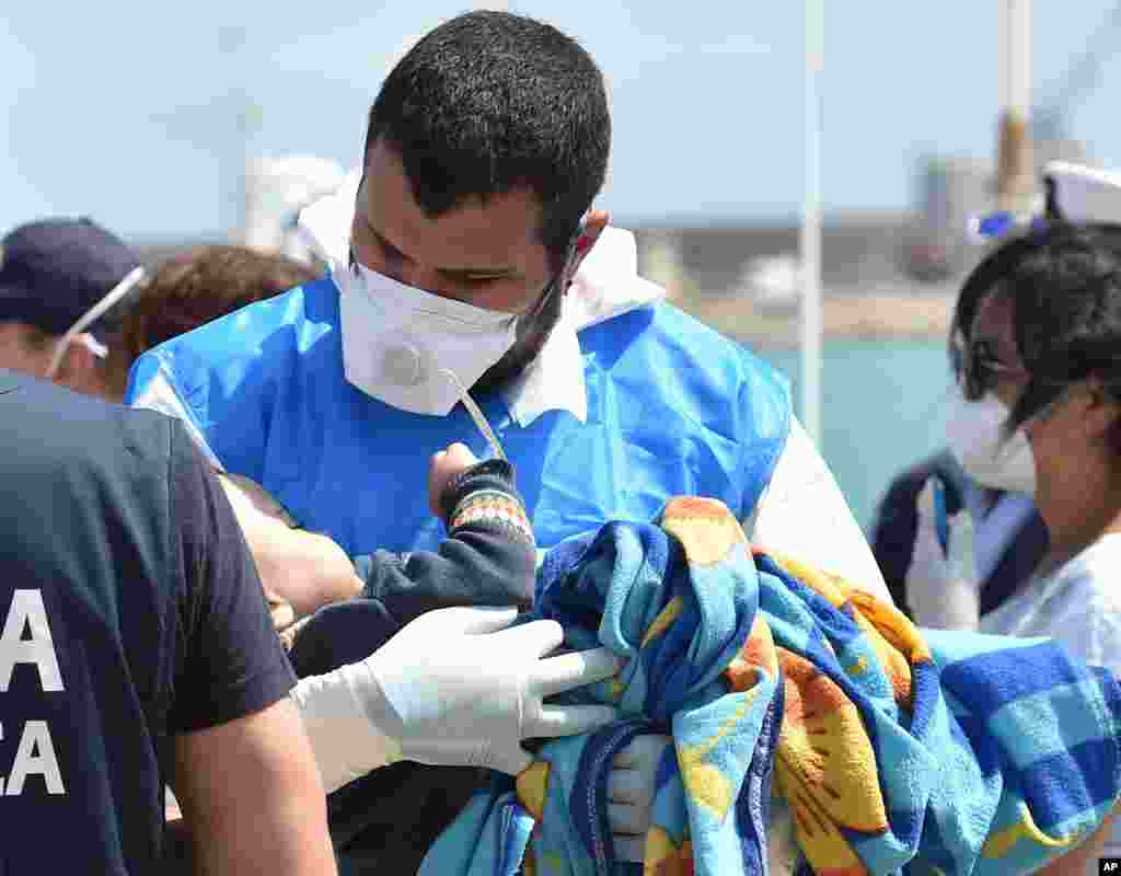 A paramedic holds a baby wrapped in a blanket as migrants arrive at Pozzallo's harbor near Ragusa, Sicily, Italy.