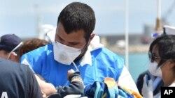 Un secouriste accueillant un bébé près de Ragusa, en Sicile