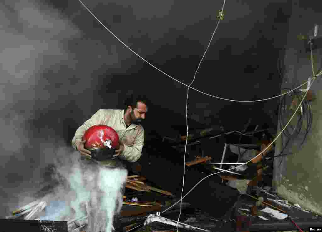 A man walks out of a burning building after a Syrian Air force air strike in Ain Tarma neighborhood of Damascus.