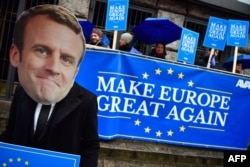 "Activists of the Avaaz civic organization wear a mask of French President Emmanuel Macron and hold up posters and a banner reading ""Make Europe Great Again."""