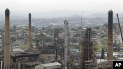 Chimneys from the Engen oil company are seen on the outskirts of the city of Durban, South Africa, Wednesday, Nov. 30, 2011. The U.N.'s top climate scientist cautioned climate negotiators Wednesday global warming is leading to human dangers and soaring fi