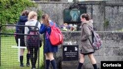 Estudiantes llegan al altar en memoria de los 800 menores encontrados en Tuam, Irlanda.