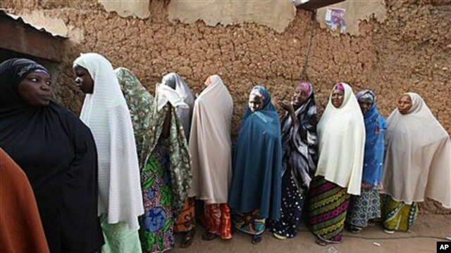 Muslim women line up  at a polling place in Daura, Nigeria, Saturday, April 16, 2011
