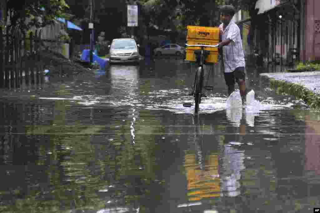 A man pushes his bicycle, carrying milk for sale, past a waterlogged street after rainfall during the monsoon season, in Mumbai, India.