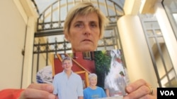 Brenda Caplen holds a photo of her son, Stuart (far left in photograph), who was killed in a collision in which alcohol was a deemed major causal factor. (D. Taylor/VOA)