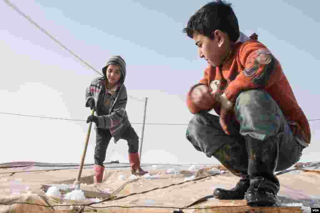 سرد موسم میں شامی باشندے اپنے گھروں کی چھتوں سے برف ہٹا رہے ہیں۔