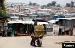 FILE - A vendor sells sugar cane in Kibera slum in Kenya's capital Nairobi, March 7, 2014.