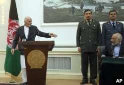 Afghan President Ashraf Ghani, left, points to Afghanistan's acting Defense Minister Masoom Stanikzai, sitting, during a press conference at the presidential palace in Kabul, Afghanistan, Sept. 29, 2015.
