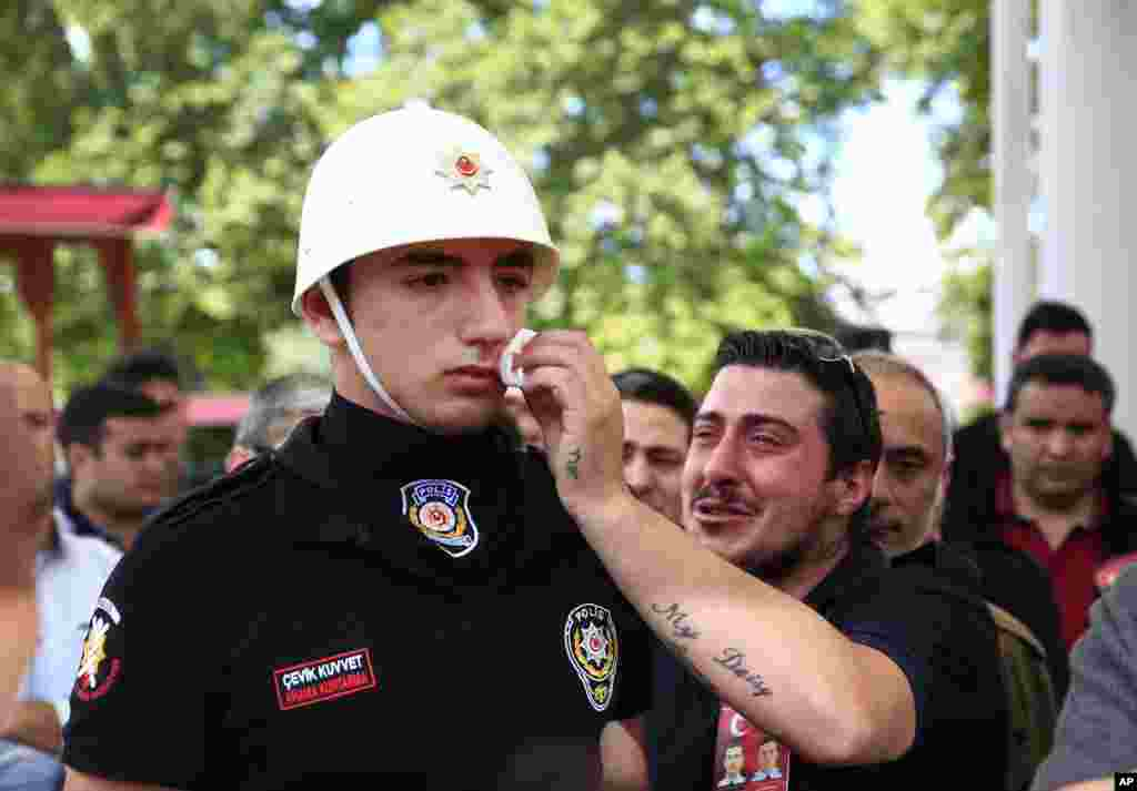A relative, right, of one of the victims of explosion, wipes the face of a Turkish police officer, serving as a honor guard, during the funeral procession for two of the victims at Fatih mosque in Istanbul.