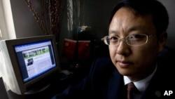 中國律師劉曉原在他的辦公室裡,旁邊的電腦顯示他的文章(2007年10月12日)