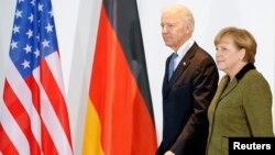 រូបឯកសារ៖ អធិការបតីអាល្លឺម៉ង់ អ្នកស្រី Angela Merkel (ស្ដាំ) និងប្រធានាធិបតីសហរដ្ឋអាមេរិក លោក Joe Biden ដែលកាលពីពេលនោះគឺជាអនុប្រធានាធិបតីសហរដ្ឋអាមេរិក ឡើងថ្លែងសុន្ទរកថានៅទីក្រុងប៊ែកឡាំង ប្រទេសអាល្លឺម៉ង់ ថ្ងៃទី១ ខែកុម្ភៈ ឆ្នាំ២០១៣។