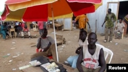 FILE - A money changer waits to do business at his open-air stall at a market in Juba, South Sudan, April 9, 2007.