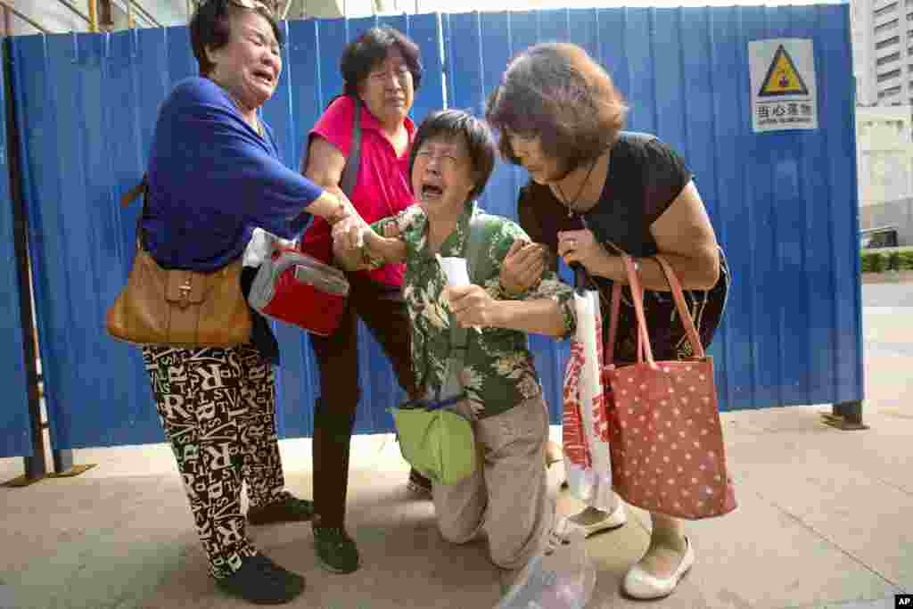 Bao Lanfang, second from right, whose daughter-in-law, son, and granddaughter were aboard Malaysia Airlines Flight 370, cries while speaking to journalists in Beijing, China.