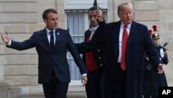 President Donald Trump is greeted by French President Emmanuel Macron after arriving at the Elysee Palace in Paris, Nov. 10, 2018.