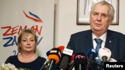 Czech President Milos Zeman, with his wife Ivana in the background, attends a news conference, after polling stations closed for the country's presidential election, in Prague, Czech Republic, Jan. 13, 2018.
