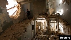 A Free Syrian Army fighter carries his weapon as he walks down the stairs of the damaged former Immigration and Passport building in Aleppo, Oct. 2, 2013.