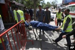 Afghan men carries a wounded man after the second blast in Kabul, Afghanistan, Monday, April 30, 2018.