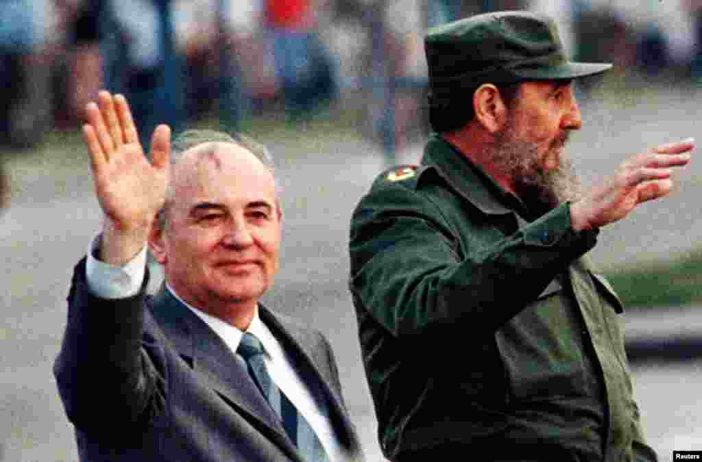 Then Soviet leader Mikhail Gorbachev and then Cuban leader Fidel Castro wave from an open top car as it drives through Havana's Revolution Square, April 2, 1989.