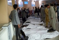 Afghan men try to identify the dead bodies at a hospital after a bomb explosion near a school west of Kabul, Afghanistan, Saturday, May 8, 2021. A bomb exploded near a school in west Kabul on Saturday, killing several people, many them young students