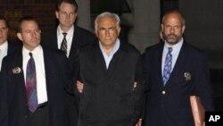 ທ່ານ Dominique Strauss-Kahn (ຄົນກາງ), ຫົວໜ້າກອງທຶນສາກົນ ຍ່າງອອກຈາກກົມຕໍາຫລວດ ທີ່ນະຄອນນີວຢອກ ວັນທີ 16 ພຶດສະພາ 2011.