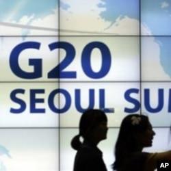 ຜູ້ຍິງສອງຄົນກໍລັງເດີນຜ່ານປ້າຍໂຄສະນາກອງປະຊຸມສຸດຍອດຂອງ ຂອງກຸ່ມ 20 ເສດຖະກິດທີ່ສໍາຄັນຂອງໂລກ ຫລື G20 ທີ່ຢູ່ໃນໜ້າຈໍ ເທິງຝາອາຄານໃຫຍ່ ແຫ່ງນຶ່ງໃນະຄອນຫລວງ ໂຊລ, ເກົາຫລີໃຕ້