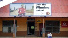 A woman sits beneath a billboard for the National Union of Mineworkers in South Africa's North West province on Oct. 13, 2012.